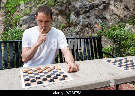Checkers table in park in Hot Springs, Arkansas with man thinking playing during summer day sitting on bench - Stock Photo