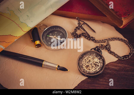 Pocket watch with old books and pen with paper map on the table by the window. Concept of travel planning. - Stock Photo