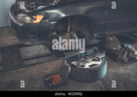 Car service. replace tires on wheels. Tire installation concept. old car is disassembled in the garage on the pit - Stock Photo