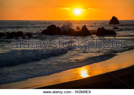 The setting sun lights up the waves of the Pacific Ocean as they crash against the rocks in the Wilson Creek Beach area along Highway 101. - Stock Photo