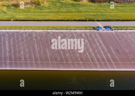 Abstract aerial view of the dam wall of a dam from the water side, aerial - Stock Photo