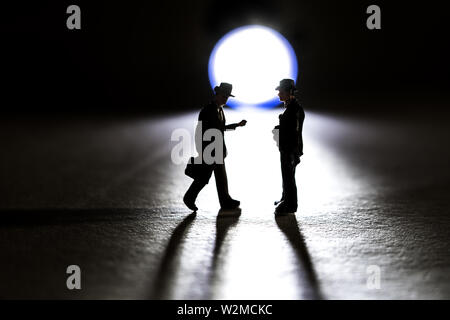 Silhouette of two business figurine walking towards each other in front of a small flashlight - Stock Photo