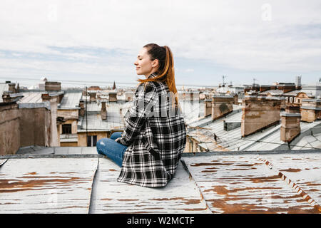 A girl on the roof of a house in solitude meditates or enjoys life or a digital detox. The search for the soul. - Stock Photo