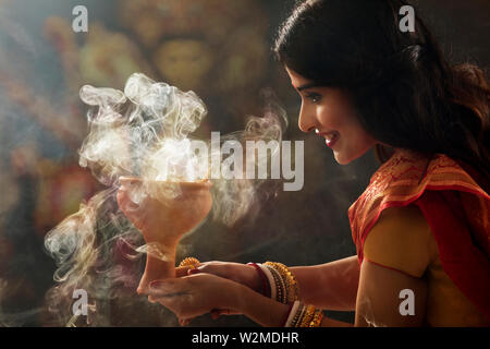 Bengali Married woman doing a Dhunuchi dance on the occasion of durga puja - Stock Photo