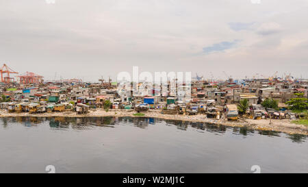 Slums in Manila near the port. Houses of poor inhabitants. A lot of garbage in the water, Philippines, top view. - Stock Photo