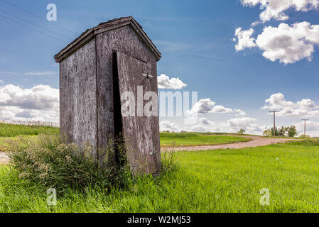 Old wooden outhouse on the prairie countryside in Saskatchewan, Canada - Stock Photo