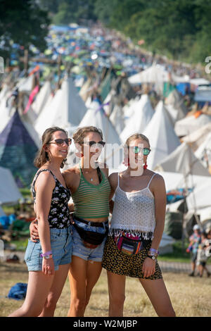 Festival-goers pose for a picture above the Tipi Village at Glastonbury 2019 - Stock Photo