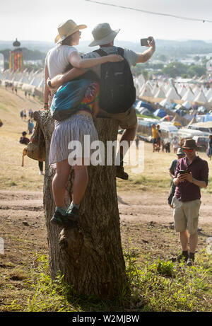 Festival goers pose for a picture above the Tipi Village at Glastonbury 2019 - Stock Photo