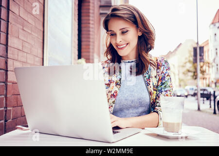 Beautiful woman working on laptop at outdoors cafe - Stock Photo