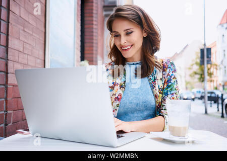 Beautiful young woman typing on laptop during coffee break at outdoors cafe - Stock Photo