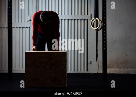 Tired sports man after box jumping exercise leaning on box. Dark picture. - Stock Photo