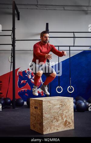 Man doing box jump exercise at gym - Stock Photo