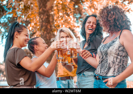 Happy group of best female friends drinking light beer - Friendship concept with young female friends enjoying time and having genuine fun at outdoor