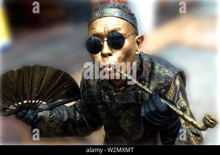 Singapore, standman in gold mandarin, OPIUM SMOKER..at Temple street, Chinatown. - Stock Photo