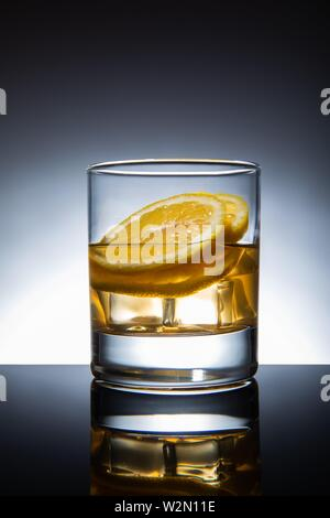 Glass of cocktail with ice-cubes and lemon, isolated. - Stock Photo