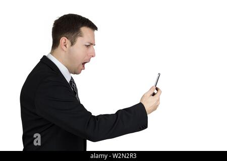 Businessman in Black Suit Holding Smartphone in Hand And Feeling Angry Against White Background. - Stock Photo