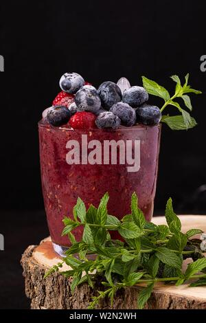 Berry smoothie decorated with frozen blueberries, raspberries and mint leaves. - Stock Photo