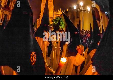 Hooded Penitents (Nazarenos) in the procession of the Brotherhood (Hermandad) La Macarena, early morning on Good Friday, Holy Week (Semana Santa), - Stock Photo