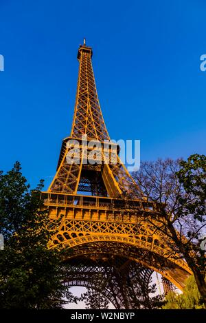 View of the Eiffel Tower from Champ de Mars Park. It is the world famous wrought-iron lattice tower that is the most famous landmark of Paris, France. - Stock Photo