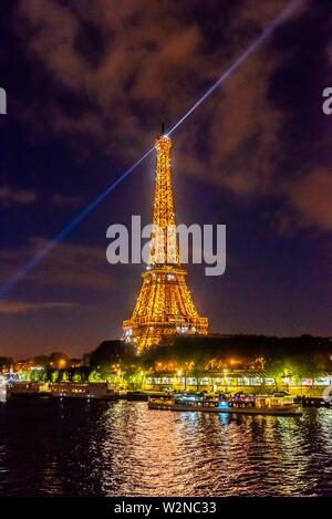 The illuminated Eiffel Tower with the River Seine in the foreground, Paris, France. - Stock Photo
