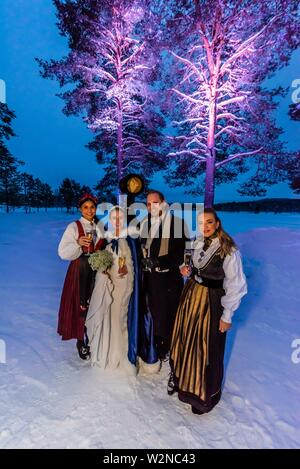 Two female guests at a Norwegian wedding wearing the bunad, the Norwegian National Costume, stand with the bride and groom before the reception, - Stock Photo