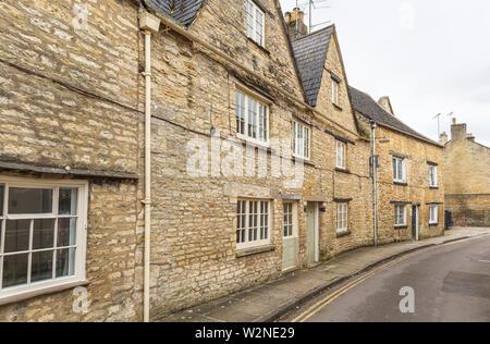 Street view of a row of traditional Cotswold stone cottages in Circencester, a town known as the Capital of the Cotswolds in east Gloucestershire, UK - Stock Photo