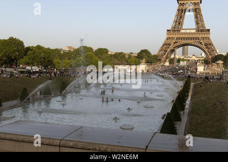 Europe, France, Paris, 2019-06, Eiffel Tower monument viewd from the Trocadero gardins. People bathing in the fountains in an effort to cool down duri - Stock Photo