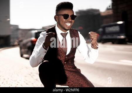 well-dressed African man celebrating success, wearing fancy red suit at street in city, in Munich, Germany. - Stock Photo