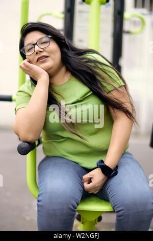 weary woman catnapping, snoozing while sitting - Stock Photo