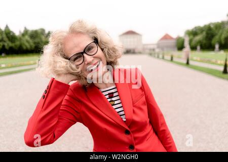 happy senior woman (67 years old) in park at touristic sight Nymphenburg palace, in Munich, Germany. - Stock Photo