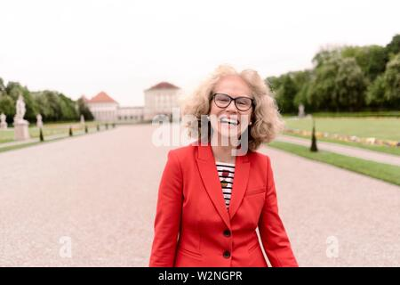 happy senior woman (67 years old) laughing in park at touristic sight Nymphenburg palace, in Munich, Germany. - Stock Photo