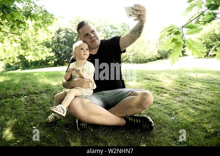 young father taking selfie with toddler son in nature, in Cottbus, Brandenburg, Germany. - Stock Photo