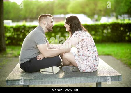 enamoured couple sitting together on ping-pong table, looking at each other - Stock Photo
