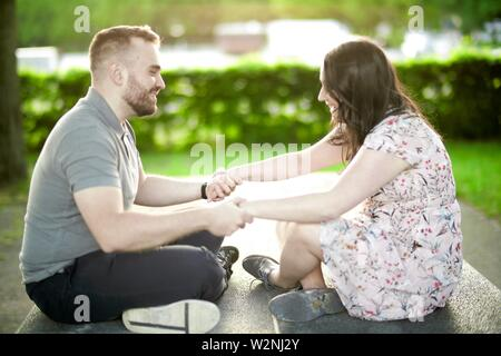 enamoured couple sitting together on ping-pong table, holding hands - Stock Photo