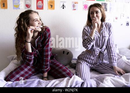 two young women in pyjamas brushing teeth while sitting on bed in bedroom Stock Photo