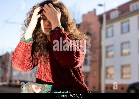 young emotional woman outdoors in city - Stock Photo