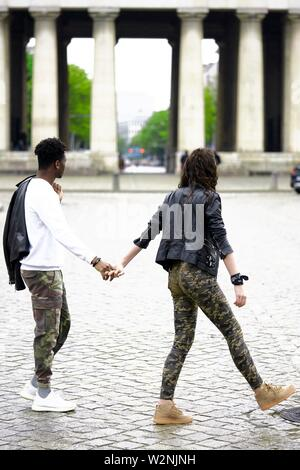 young mixed race couple crossing street in city, holding hands, in front of historical landmark Königsplatz, in Munich, Germany