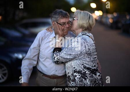 senior woman whispering old secrets in ear of attentive lover, at night on street in city - Stock Photo