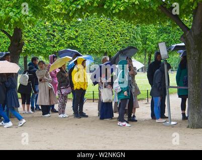 line up in rain for Orangerie Museum, Paris, France. - Stock Photo