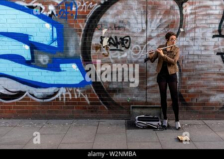 Berlin, Germany. Young woman playing classical music pieces on her flute, standing in front of a huge Graffity, earning a modest buck. - Stock Photo