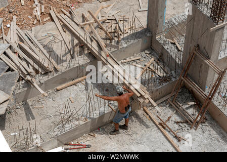 Crete, Greece. June 2019. A builder on site working with recycled  wooden planks - Stock Photo