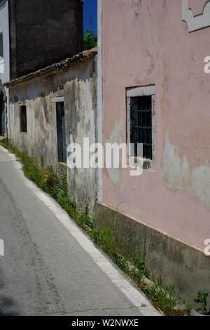 Corfu.road and houses leading into the hillside village of Avliotes.the houses on road side are very basic. - Stock Photo