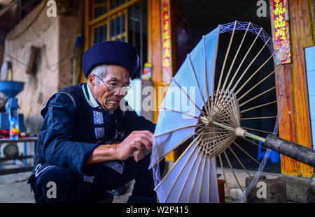 (190710) -- QIUBEI, July 10, 2019 (Xinhua) -- Zhang Ronghua makes an oil-paper umbrella in Xiangyang Village of Qiubei County, Zhuang and Miao Autonomous Prefecture of Wenshan, southwest China's Yunnan Province, July 9, 2019. Zhang Ronghua, 89, and his grandson Zhang Guoqing are the only inheritors of traditional oil-paper umbrella making in Xiangyang Village.    Xiangyang Village has an over 400-year history of making handcrafted oiled paper umbrellas with bamboo stands.      Made of oiled paper and bamboo frame, oil-paper umbrella is a traditional Chinese handicraft. The craftsmanship includ - Stock Photo