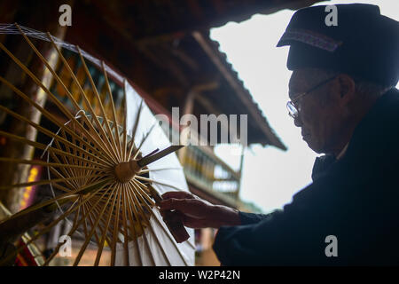 (190710) -- QIUBEI, July 10, 2019 (Xinhua) -- Zhang Ronghua glues the paper cover onto the skeleton to make an oil-paper umbrella in Xiangyang Village of Qiubei County, Zhuang and Miao Autonomous Prefecture of Wenshan, southwest China's Yunnan Province, July 9, 2019. Zhang Ronghua, 89, and his grandson Zhang Guoqing are the only inheritors of traditional oil-paper umbrella making in Xiangyang Village.    Xiangyang Village has an over 400-year history of making handcrafted oiled paper umbrellas with bamboo stands.      Made of oiled paper and bamboo frame, oil-paper umbrella is a traditional Ch - Stock Photo