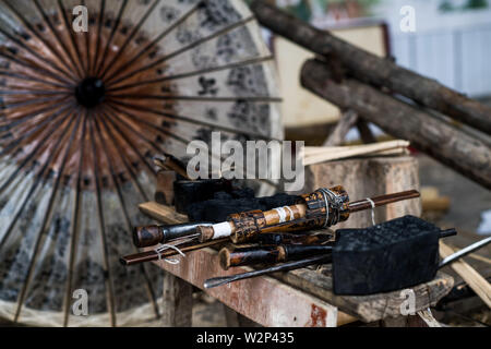 (190710) -- QIUBEI, July 10, 2019 (Xinhua) -- Photo taken on July 9, 2019 shows tools used to make oil-paper umbrellas in Xiangyang Village of Qiubei County, Zhuang and Miao Autonomous Prefecture of Wenshan, southwest China's Yunnan Province. Zhang Ronghua, 89, and his grandson Zhang Guoqing are the only inheritors of traditional oil-paper umbrella making in Xiangyang Village.    Xiangyang Village has an over 400-year history of making handcrafted oiled paper umbrellas with bamboo stands.      Made of oiled paper and bamboo frame, oil-paper umbrella is a traditional Chinese handicraft. The cra - Stock Photo