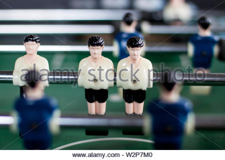 Concept: Team work. Fooseball - Old used table football table. Close up of two white tshirt team players.  Soccer players planning strategies. Play on - Stock Photo