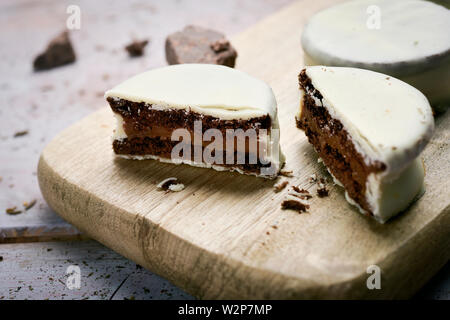 some argentinean-uruguayan alfajores filled with dulce de leche and coated with a white coating on a wooden chopping board, on a rustic table - Stock Photo