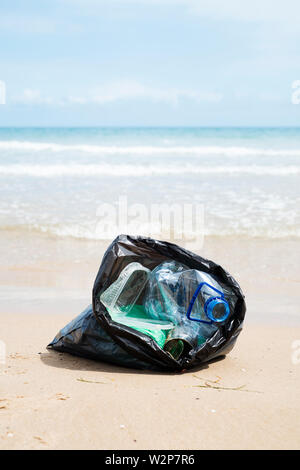 closeup of a gray plastic bag with collected garbage on the sand of a lonely beach, next to the water, with the horizon in the background, and some bl - Stock Photo