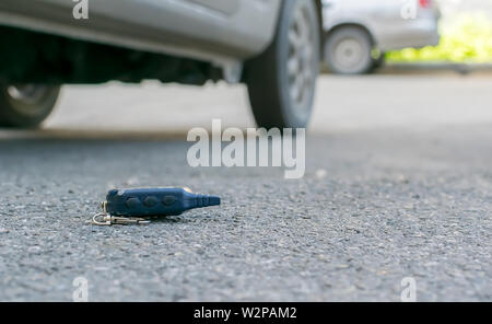 The lost keychain, car alarm remote, lies on the asphalted sidewalk of the road, near an entrance of a house with the parked cars - Stock Photo