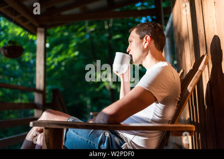 Man sitting relaxing on rocking chair on porch of house in morning wooden cabin cottage drinking coffee from cup Stock Photo